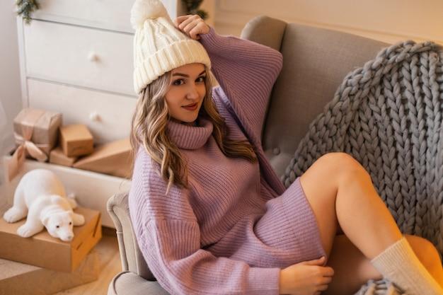 Giovane bella donna felice con un cappello lavorato a maglia in un maglione vintage e calzini si siede su una sedia con un plaid a casa. buon natale e vacanze invernali