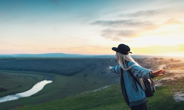 Giovane ragazza bionda felice con zaino nero e berretto, tenendosi per mano come un aereo sulla cima delle colline al tramonto. concetto di viaggio.