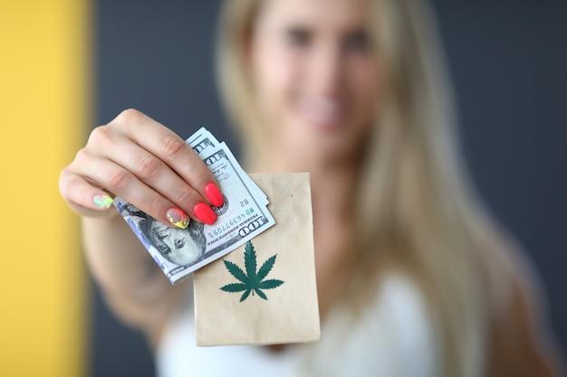 Giovane donna bionda felice che tiene un pacco con marijuana e consegna di denaro di cannabis legale