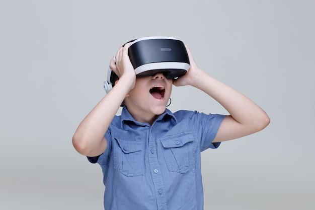 Giovane ragazzo felice in bicchieri di realtà virtuale su sfondo grigio