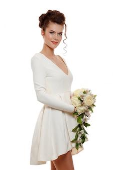 Giovane sposa felice in abito corto bianco con un mazzo di fiori