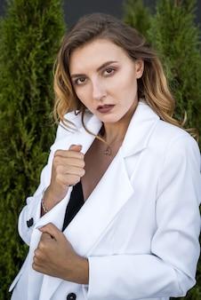 Giovane donna castana felice in vestito bianco che posa alla natura, cedro bianco, ora legale