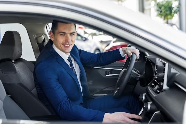 Giovane e uomo d'affari felice che si siede nella nuova automobile in showroom