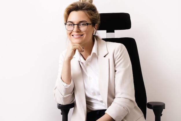 Giovane e felice imprenditrice seduta sulla sedia da ufficio office