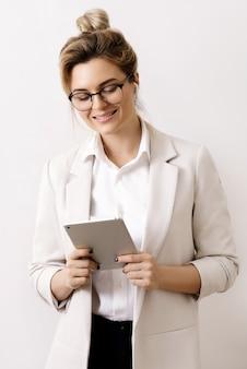 Giovane e felice imprenditrice con un tablet pc su grigio