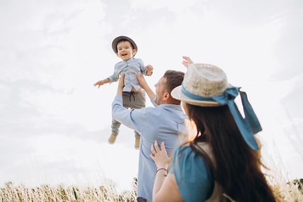Giovani coppie caucasiche felici con il neonato. genitori e figlio si divertono insieme. la madre e il padre giocano con il bambino all'aperto