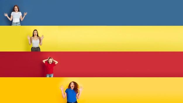 Giovani bambini caucasici felici che gesturing isolati su fondo multicolore dello studio. emozioni umane