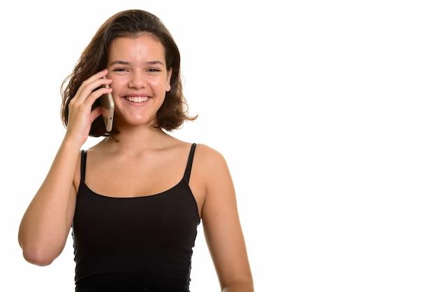 Giovane adolescente caucasico felice che sorride mentre parla sul telefono cellulare