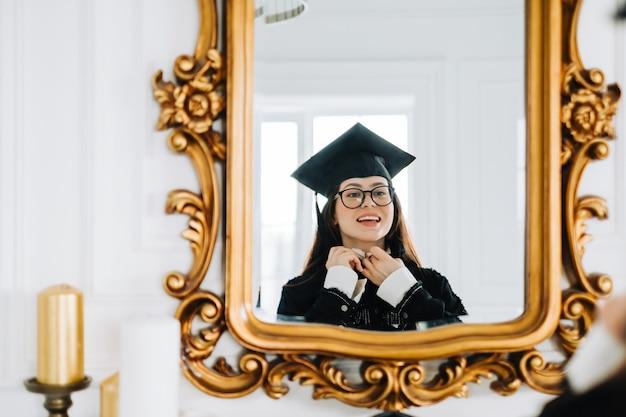 La giovane studentessa caucasica felice si prepara a celebrare la cerimonia di laurea.