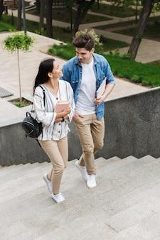 Giovani studenti felici allegri incredibili coppie amorose all'aperto all'aperto camminando per gradini con i libri.