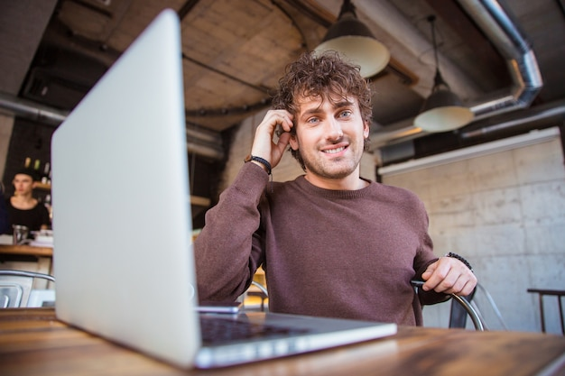Giovane felice contenuto attraente gioioso sorridente bell'uomo che lavora utilizzando il computer portatile