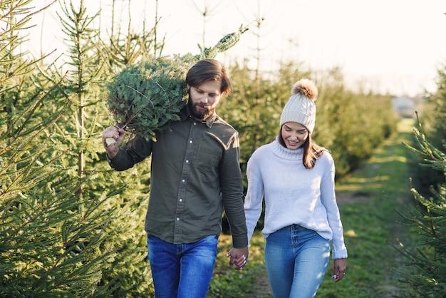 La giovane coppia felice ha acquistato l'albero di natale fresco alla piantagione che prepara le feste. buone vacanze invernali