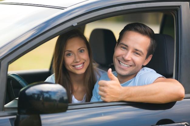 Giovane coppia felice in macchina sorridente - concetto di acquisto di auto