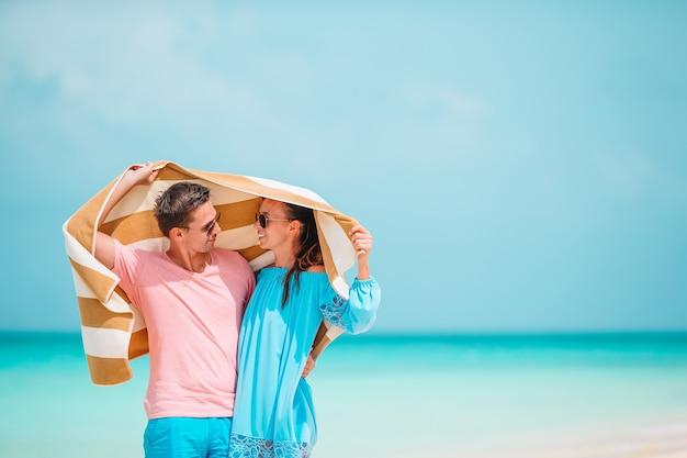 La giovane coppia felice copre dalla pioggia con un asciugamano sulla spiaggia