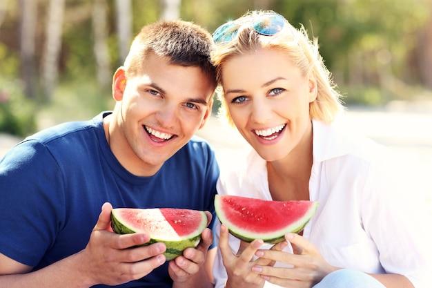 Una giovane coppia felice che mangia anguria in spiaggia