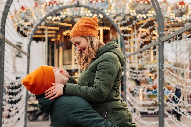 Giovani coppie felici che hanno divertimento insieme a un mercatino di natale