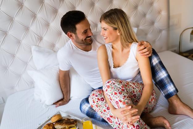 Giovane coppia felice che ha momenti romantici in camera da letto