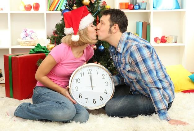 Giovane coppia felice che tiene l'orologio vicino all'albero di natale a casa
