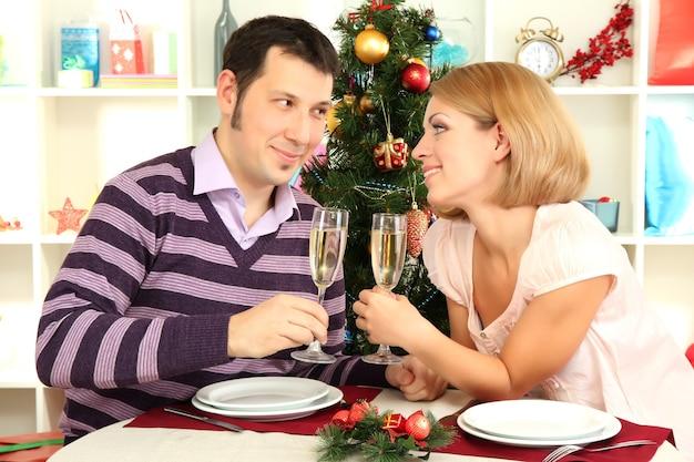 Giovane coppia felice che tiene bicchieri di champagne al tavolo vicino all'albero di natale