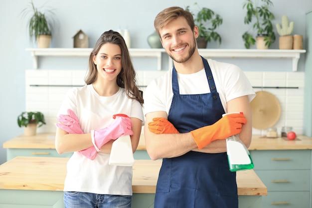 La giovane coppia felice si diverte mentre fa le pulizie a casa.