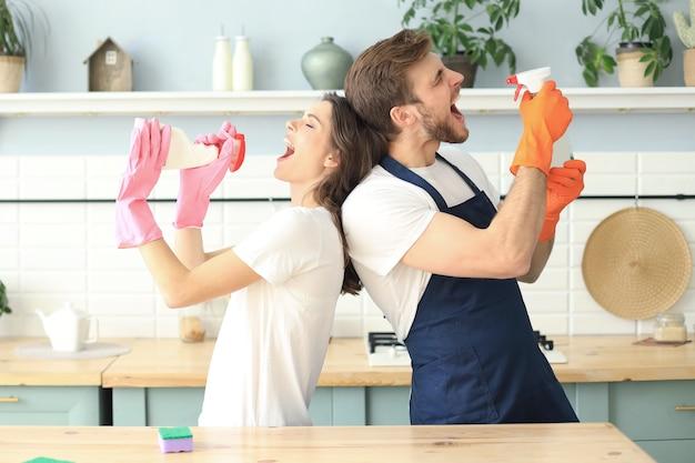 La giovane coppia felice si diverte mentre fa le pulizie e canta a casa.
