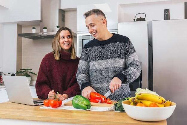 La giovane coppia felice sta ridendo e preparando cibo sano nella loro cucina e leggendo le ricette sul notebook