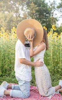 Giovane coppia felice che si bacia su una coperta da picnic, coprendosi il viso con un cappello estivo