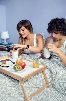 Giovane coppia felice innamorata che fa colazione a letto servita su un vassoio a casa. concetto di stile di vita domestico delle coppie.