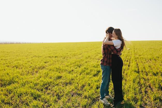 Giovani coppie felici nell'amore che abbraccia in un campo verde nella giornata di sole primaverile.