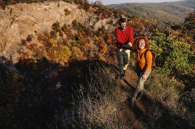 Giovani coppie felici nell'amore che trascorrono bella giornata di sole autunnale nella natura. coppia tenendosi per mano e scalando la collina.