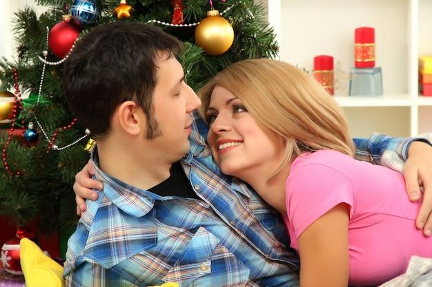 Giovane coppia felice vicino a un albero di natale a casa