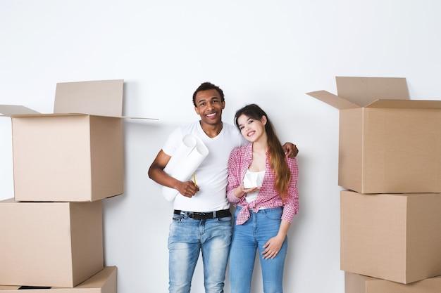 Giovani coppie felici in una nuova casa. pensa agli interni. in movimento.
