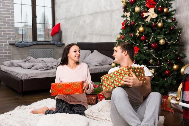 Giovani coppie felici in pigiama che ridono e si rallegrano dei loro regali mentre sono seduti sul tappeto vicino all'albero di natale nella stanza in stile loft