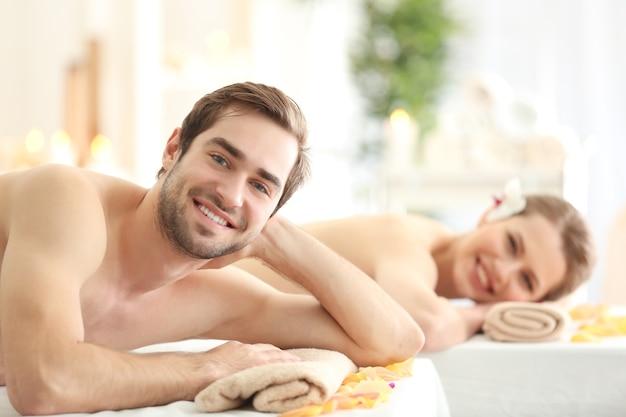 Giovani coppie felici che si rilassano nel salone della stazione termale