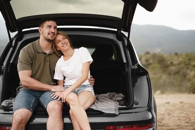 Giovane coppia felice in viaggio seduto nel bagagliaio di un'auto all'aperto