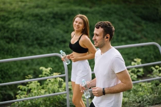 Giovane coppia felice che corre nel parco cittadino con una bottiglia d'acqua in mano, sport congiunti, allegria, stile di vita sportivo cittadino