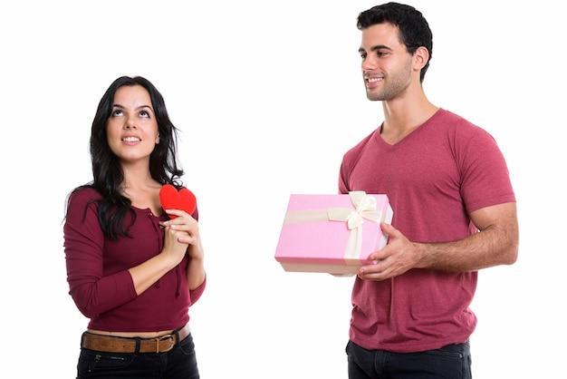 Giovani coppie felici che sorridono con l'uomo che dà il contenitore di regalo e il pensiero della donna
