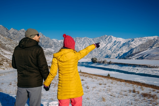 Giovani coppie felici in montagne nevose con lo spazio della copia. ragazzo e ragazza in abiti invernali luminosi guardano le cime innevate. vacanze di natale.