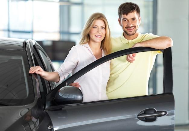 Giovane coppia felice in piedi in macchina sorridente - concetto di acquisto di auto