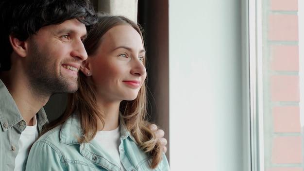 Coppia giovane e felice in piedi insieme, guardando fuori da una finestra.