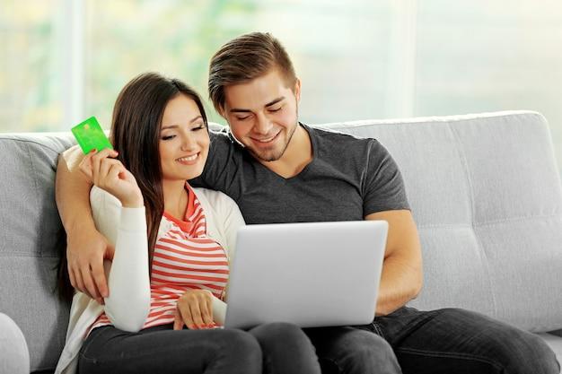 Giovane coppia felice utilizzando la carta di credito con il computer portatile a casa su sfondo chiaro