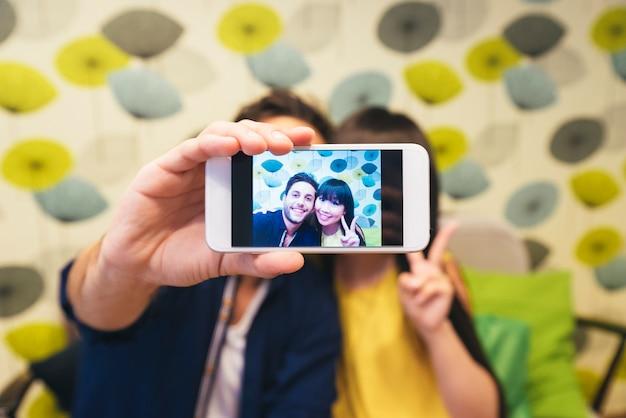 Giovani coppie felici che utilizzano smartphone al bar. sono in caffetteria