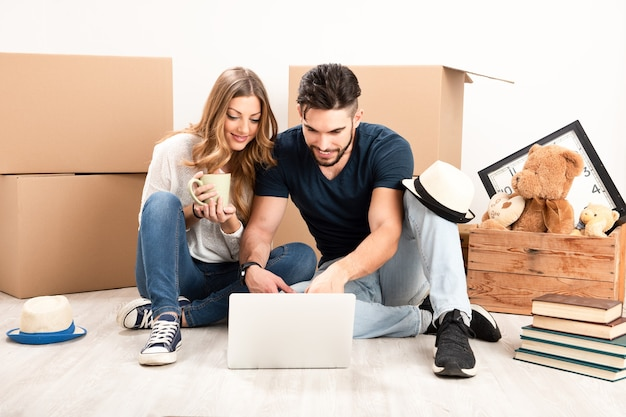 Giovane coppia felice con tablet pc e scatole per trasloco seduta sul pavimento nella nuova casa