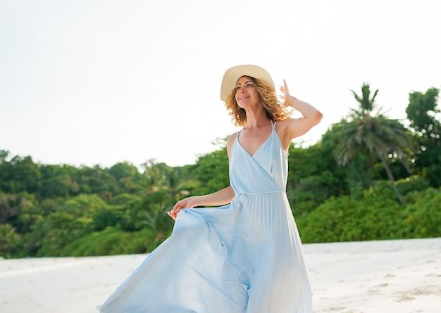Giovane ragazza riccia felice sull'isola tropicale in abito di chiffon blu. b