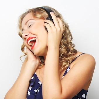 Giovane donna riccia felice con le cuffie che ascolta la musica