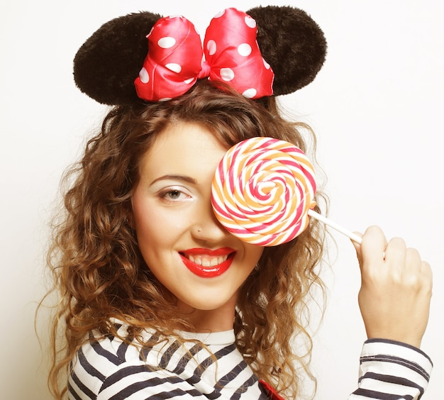 Giovane donna riccia felice con le orecchie di topo che tengono lecca-lecca