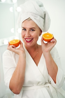 La giovane donna energica felice in una veste bianca e un asciugamano sulla sua testa tiene metà delle arance nel suo h