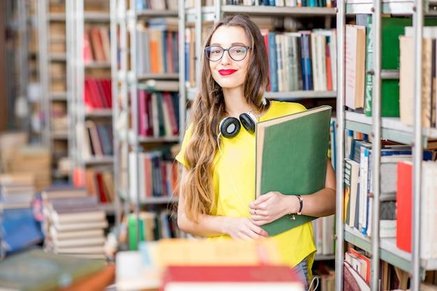 Giovane studentessa felice ed entusiasta che legge libri nella vecchia biblioteca