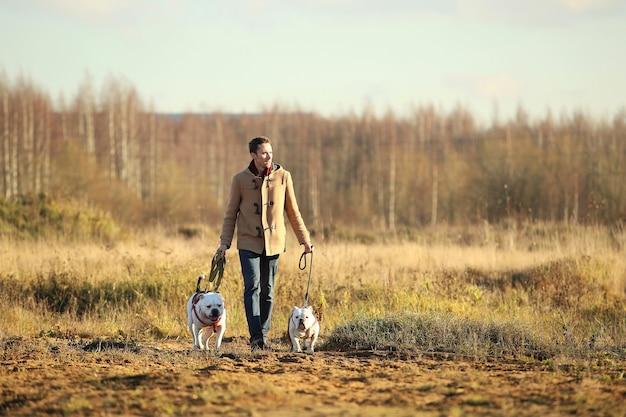 Giovane europeo felice in piedi con due cani al guinzaglio