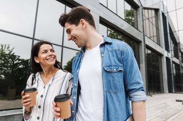 Giovani felici eccitati incredibili coppie amorose studenti all'aperto fuori a piedi per strada bevendo caffè parlando tra loro.